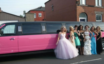 Prom girls pose with pink limo